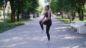Junge Frau der Trainingseignungsverletzungen mit den Schmerz im Bein mischt während der Übung draußen mit stock footage