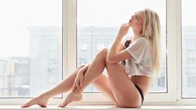 Junge Frau in der Unterwäsche, die auf Fensterbrett sitzt Stockfotografie