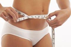 Junge Frau in der Unterwäsche mit messendem Band stockbilder