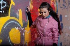 Junge Frau in der Verzweiflung, die gegen eine Backsteinmauer sitzt Lizenzfreies Stockbild