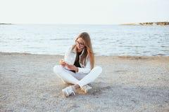 Junge Frau in der weißen Jacke ist, betrachtend sitzend und das Telefon Lizenzfreies Stockbild