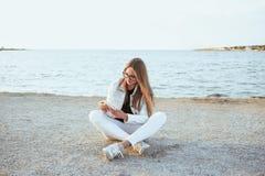 Junge Frau in der weißen Jacke ist, betrachtend sitzend und das Telefon Stockfoto