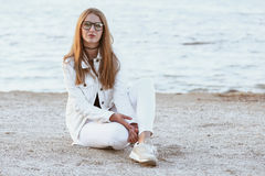 Junge Frau in der weißen Jacke ist, betrachtend sitzend und die Kamera Lizenzfreie Stockfotos