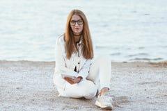 Junge Frau in der weißen Jacke ist, betrachtend sitzend und die Kamera Lizenzfreies Stockfoto