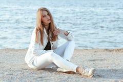 Junge Frau in der weißen Jacke ist, betrachtend sitzend und die Kamera Lizenzfreies Stockbild