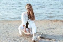 Junge Frau in der weißen Jacke ist, betrachtend sitzend und die Kamera Stockfotografie