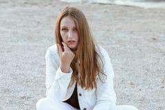 Junge Frau in der weißen Jacke ist, betrachtend sitzend und die Kamera Stockfotos