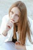Junge Frau in der weißen Jacke ist, betrachtend sitzend und die Kamera Stockfoto