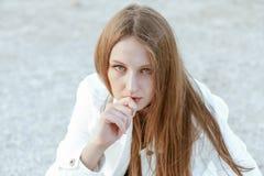 Junge Frau in der weißen Jacke ist, betrachtend sitzend und die Kamera Stockbilder