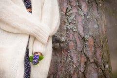 Junge Frau in der weißen Wolljacke, die nahe einem alten Baum steht und schöne Schneeglöckchen in ihren Händen hält lizenzfreie stockbilder