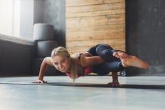 Junge Frau in der Yogaklasse, Acht-Winkel-Haltung asana Lizenzfreie Stockfotografie