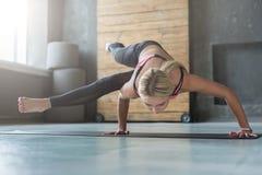 Junge Frau in der Yogaklasse, Acht-Winkel-Haltung asana Stockbild