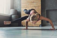 Junge Frau in der Yogaklasse, Acht-Winkel-Haltung asana Stockbilder