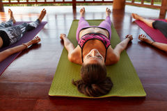 Junge Frau an der Yogaklasse, die savasana tut Stockfoto