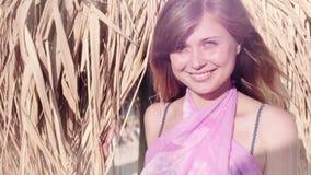 Junge Frau der Zeitlupe kommt von unterhalb eines Strohregenschirmes heraus, der auf dem Strand steht stock video footage