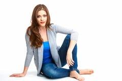 Junge Frau der zufälligen Art, die auf weißem Boden sitzt Lizenzfreie Stockfotos