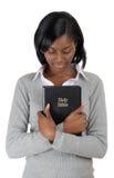 Junge Frau des Afroamerikaners, die eine Bibel anhält Stockfoto