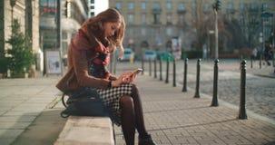 Junge Frau des attraktiven Brunette, die Telefon in einer Stadt verwendet Stockfoto