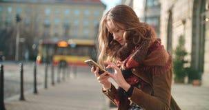 Junge Frau des attraktiven Brunette, die Telefon in einer Stadt verwendet Lizenzfreie Stockfotos