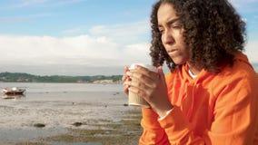 Junge Frau des Biracial Afroamerikanermädchenjugendlichen, die orange Hoodie, trinkenden zum Mitnehmen Kaffee durch einen Hafen t stock video
