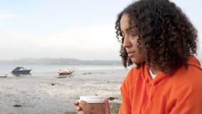 Junge Frau des Biracial Afroamerikanermädchenjugendlichen, die orange Hoodie, trinkenden zum Mitnehmen Kaffee durch einen Hafen t stock video footage