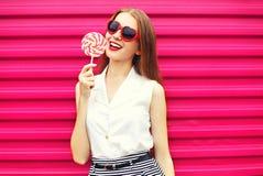 Junge Frau des Bonbons recht mit Lutscher über Rosa stockfotografie