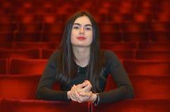 Junge Frau des Brunette, die in der leeren roten Theaterhalle sitzt Stockfoto