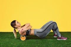Junge Frau des erstaunlichen Sitzes des Fotos Übung mit Schaumrolle auf grünem Gras über gelbem Hintergrund tun stockfotos