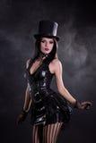 Junge Frau des Fetisches im schwarzen Kleid und im tophat Stockfotos