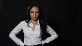 Junge Frau des frustrierten Umkippens, welche die Kamera lokalisiert über schwarzem Hintergrund betrachtet stock footage