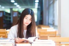 Junge Frau des glücklichen asiatischen Studenten, die mit Buch in der Bibliothek denkt lizenzfreies stockbild