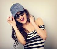 Junge Frau des glücklichen Genusses in der Sonnenbrille und in der blauen Baseballmütze Stockfoto
