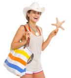 Junge Frau des glücklichen Strandes, die Starfish hält Lizenzfreies Stockfoto