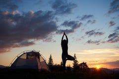 Junge Frau des hinteren Ansichtschattenbildes, die auf Bein in der Yogabaumhaltung an der Spitze des Hügels nahe Zelt steht Stockfotografie