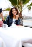 Junge Frau des Hippies, die ein Foto von an ihrem Handy schaut spielerisch macht Stockfotos