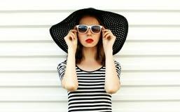 Junge Frau des Modeporträts im schwarzen Sommerstrohhut, der auf weißer Wand aufwirft lizenzfreie stockbilder