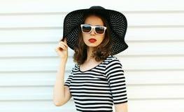 Junge Frau des Modeporträts im schwarzen Sommerstrohhut, der auf weißer Wand aufwirft stockfotografie