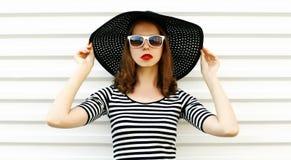 Junge Frau des Modeporträts im Sommerstrohhut, der auf weißer Wand aufwirft stockfoto