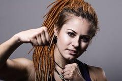 Junge Frau des Nahaufnahmeporträts mit Dreadlocks in einem Fighting stan Stockbild