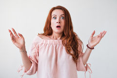Junge Frau des Porträts mit dem langen gelockten roten Haar, das aufgeregte Holding schaut, die ihr Mund lokalisiert auf weißer W Lizenzfreies Stockbild