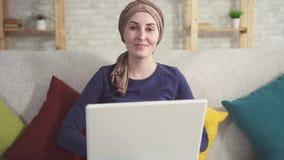 Junge Frau des Porträts mit Krebs in einem Schal nach Chemotherapie mit einem Laptop stock footage
