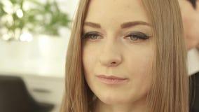 Junge Frau des Porträts während des Hairstyling im Frisörsalonabschluß oben Herrenfriseur, der nachher Frisur für langes Haar tut stock video footage