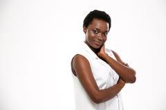 Junge Frau des reizend glücklichen Afroamerikaners, die mit den Händen gefaltet steht Lizenzfreies Stockfoto