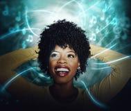Junge Frau des schönen Afroamerikaners, die strömende on-line-Musik hört stockfotografie