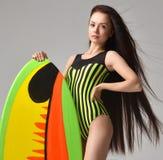 Junge Frau des schönen Brunette mit dem langem Haar und Surfbrett Lizenzfreies Stockfoto