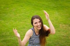 Junge Frau des schönen glücklichen Brunette, die draußen auf grünem Gras lächelt lizenzfreies stockbild