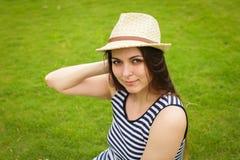 Junge Frau des schönen glücklichen Brunette im Weidenhut draußen lächelnd auf grünem Gras stockfoto