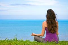 Junge Frau des schönen Pass-Sitzes, die draußen meditiert Stockbilder