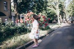 Junge Frau des schönen sinnlichen Brunette in der weißen Bluse und Rock mit Blumen tanzen nah an rotem Rosenbusch Stockbilder