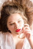 Junge Frau des schönen, sinnlichen verlockenden Brunette mit dem roten Lippenstift, der Kameranahaufnahmeporträt betrachtet Stockbild
